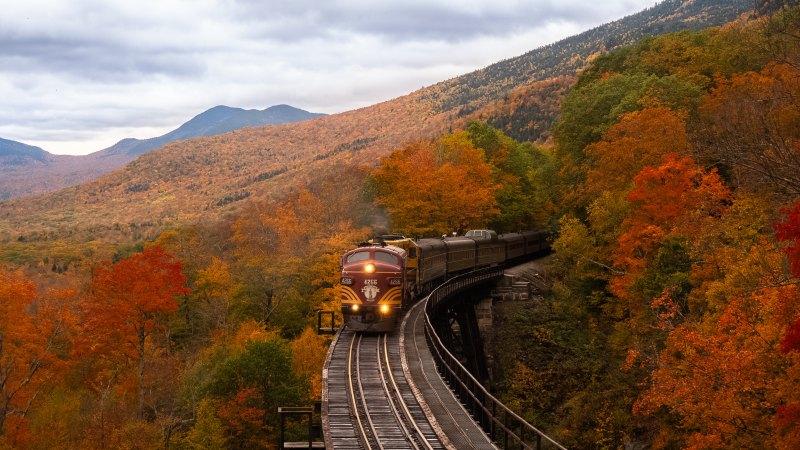 trem passa por montanha no outono